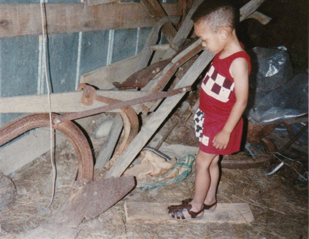 Jack Johnson's Great Grandson Marcus Johnson in barn looking at plows